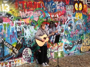Man Playing Beatles Songs in Front of Lennon Wall